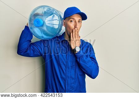 Bald courier man with beard holding a gallon bottle of water for delivery covering mouth with hand, shocked and afraid for mistake. surprised expression