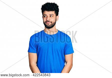 Young arab man with beard wearing casual blue t shirt smiling looking to the side and staring away thinking.