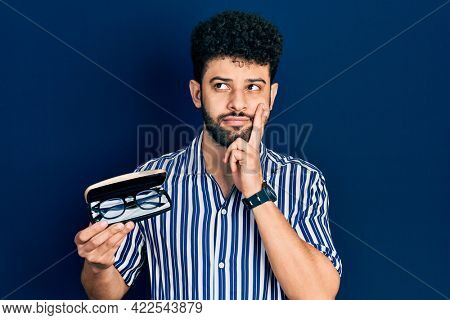 Young arab man with beard holding glasses in eyewear case serious face thinking about question with hand on chin, thoughtful about confusing idea