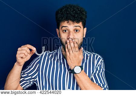 Young arab man with beard holding invisible aligner orthodontic and braces covering mouth with hand, shocked and afraid for mistake. surprised expression
