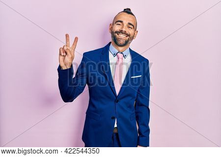 Young hispanic man wearing business suit and tie showing and pointing up with fingers number two while smiling confident and happy.