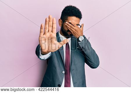 Handsome hispanic business man with beard wearing business suit and tie covering eyes with hands and doing stop gesture with sad and fear expression. embarrassed and negative concept.