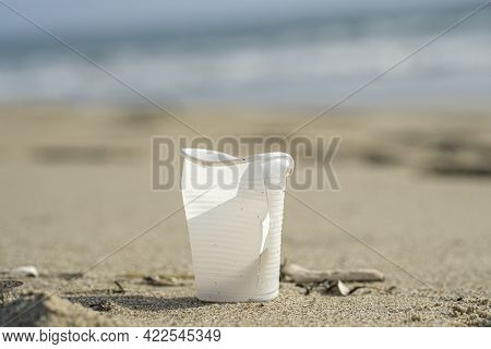 Isolated Plastic Cup Discarded On Sea Coast Ecosystem, Nature Waste Pollution