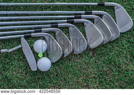 Golf Equipment. Golf Ball And Golf Club On Green Grass Background. Collection Of Golf Equipment Rest