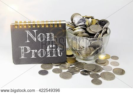 Coins In Cups And Nonprofit Writing On Notebooks