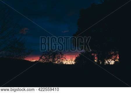 Intense Sunrise With Clouds Rolling Over The Mountains And Thick Vegetation Shot In Tasmania, Austra