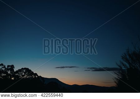 Sunrise With Clouds Rolling Over The Mountains And Thick Vegetation Shot In Tasmania, Australia
