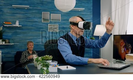 Senior Man Using Virtual Reality Goggles In Living Room Gesturing Sitting In Home Workplace. Retired