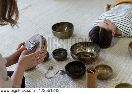 Tibet Singing Bowls Massage And Sound Therapy Concept. Closeup Of Healer Using Traditional Nepal Mus