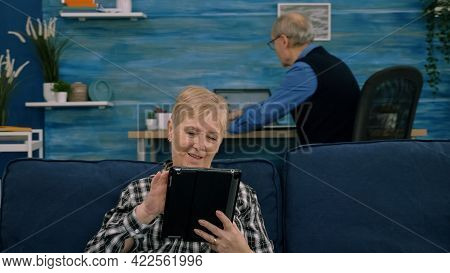Senior Woman Reading Emails On Digital Tablet Sitting On Sofa At Home, While Senior Adult Man Workin
