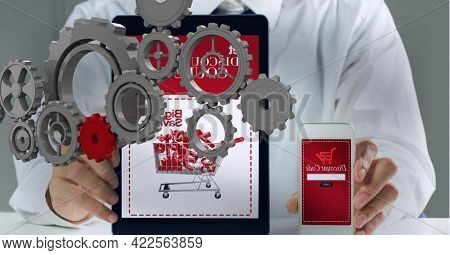 Composition of 3d cogs over midsection of businessman online shopping with tablet and smartphone. global business communication and networking technology concept digitally generated image.