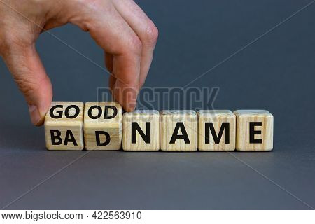 Good Or Bad Name Symbol. Businessman Turns Wooden Cubes And Changes Words 'bad Name' To 'good Name'.