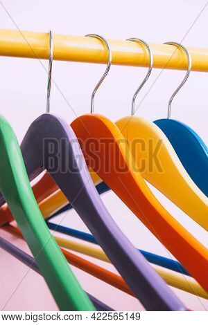 Set Of Several Bright Multicolored Wooden Clothes Hangers Hang On A Yellow Rack