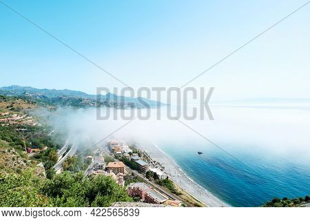 Sicily. Ionian Sea Cost Line View From Top On Santa Teresa Di Riva Covered By Fog. Beauty In Sicily