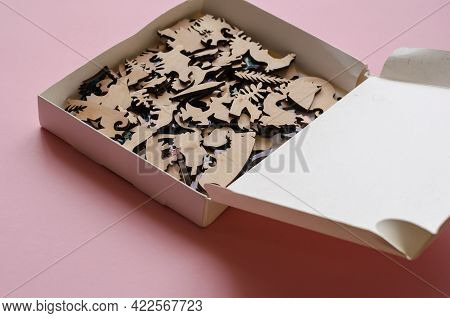Open-box With A Wooden Puzzle On A Pink Background. A Complex Puzzle Of Highly Accurate Shapes And A