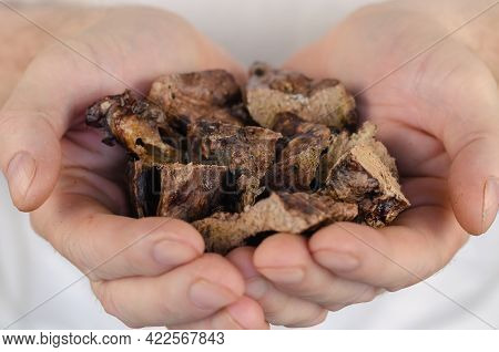 A Close-up Of Popular Dog Treats In Hand. A Man Is Holding Full Palms Of Dried Beef Lungs. Training