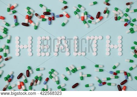 Word Health Is Laid Out From White Pills On Background Of Multicolored Capsules Closeup Background