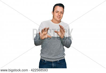 Handsome young man wearing casual winter sweater disgusted expression, displeased and fearful doing disgust face because aversion reaction. with hands raised