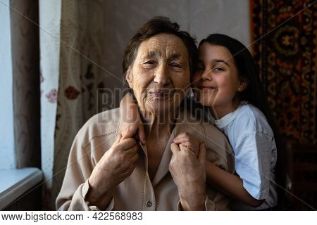 Little Baby Girl And Very Old Woman. Little Child Hugging Grandmother. Granddaughter