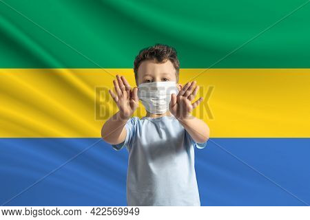 Little White Boy In A Protective Mask On The Background Of The Flag Of Gabon. Makes A Stop Sign With