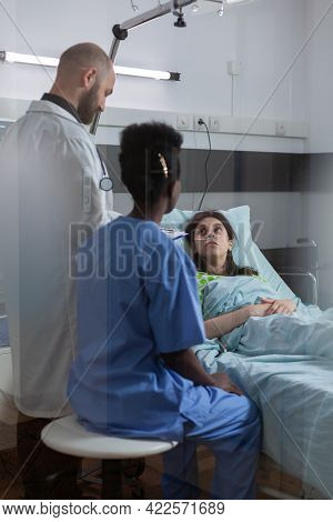 Sick Woman Patient Resting In Bed Talking With Medical Doctor Explaining Disease Symptom While Writi
