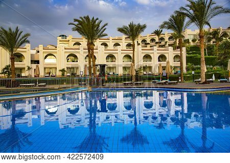 Africa, Egypt, May, 2021 - Swimming Pool With The Some Beach Lounges With A View On Green Palms At T