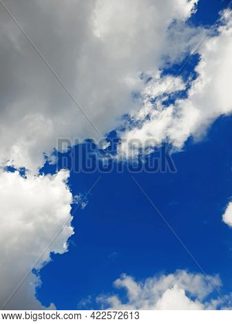 White Clouds Against The Blue Sky, Vertical Image Oriented. White Clouds On Clear Blue Sky, Bottom V