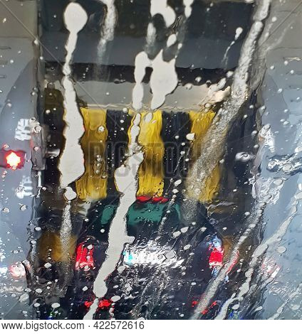 A Car Is Washing In A Car Wash, A View Through The Wet Windshield. The Brushes Washing A Car In A Ca