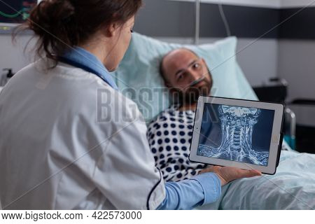 Physician Practitioner Doctor Analyzing Bones Radiography Using Tablet Computer In Hospital Ward. Ho