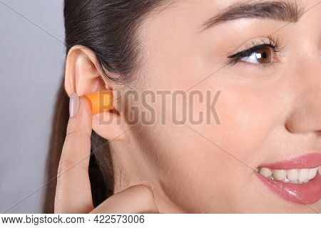 Young Woman Inserting Foam Ear Plug On Grey Background, Closeup