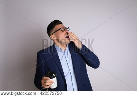 Tired Businessman With Mug Of Drink Yawning On Light Grey Background