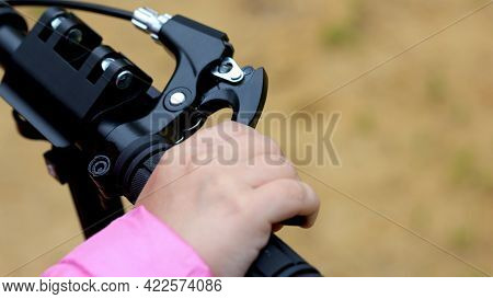 Child Hand Pressing Brake On A Scooter. Close-up View.