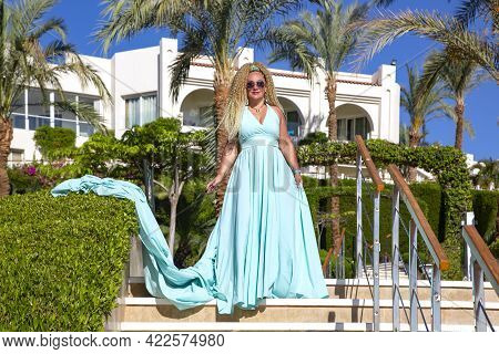 A Beautiful Slender Woman With Curly Hair In A Blue Long Evening Luxurious Dress On Background Of A