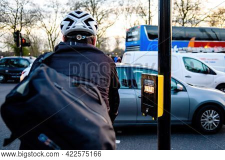 Rear View Of Cyclist With Helmet Waiting At The Crossroad Pedestrians Street Crossing With Light On