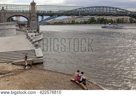 Moscow, Russia - May 15, 2021: View Of Pushkin Embankment. People Sits On Log By The River. Ship Sai
