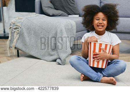 Positive Child Holds Large Popcorn Bucket While Watching A Cartoon Movie At Home Cinema. African Ame