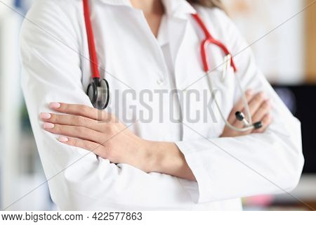 Woman Doctor In White Coat And Stethoscope Stands With Folded Arms