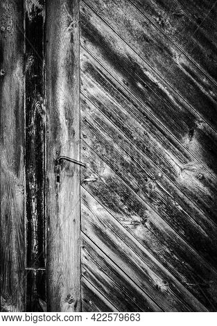 Very Old Wooden Door With Metal Handle And Almost No Paint, Black And White Image
