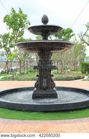 Beautiful Fountain In The Park Garden. Water Flows From The Fountain.