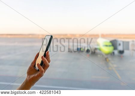 Close-up Shot Of Female Hand Holding Smart Phone By Window At Airport. Area With Airplane In Backgro