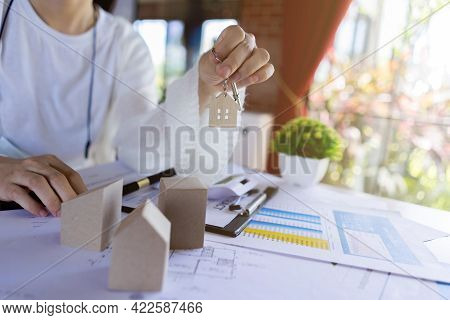 Real Estate Or Housing Agents Showing House Keys And Discussing About Loans And Interest Rates For B