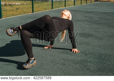 Sportswoman In Black Tight Tracksuit Stretching On The Playground. Fitness Young Woman Workout Yoga