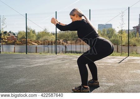 Street Workout For Butt And Legs. Fitness Young Woman Doing Squats, Morning Outdoors. Sportswoman In