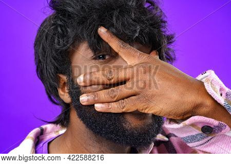 African Young Man Closing His Face With Palm And Peeping