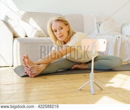 Flexible Retired Woman Exercising On Yoga Mat In Living Room, Watching Online Class On Smartphone, S