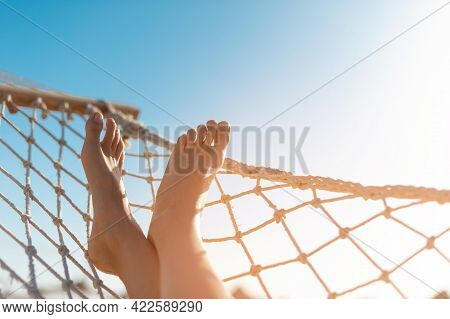 View Of Woman Relaxing On Hammock. Low Angle View. Beautiful Female Feet Relaxing In A Hammock On Th