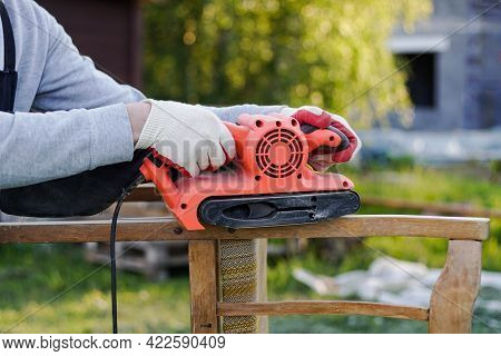 Close Up Of Carpenter Using Electric Sander For Restoration Of Old Chair