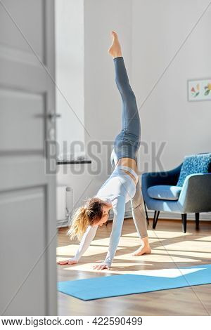 fitness, sport and healthy lifestyle concept - woman doing yoga exercise at home or at studio