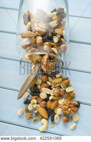 A Mixture Of Loose Nuts. Storage Of Nuts In A Glass Jar, On A Wooden Table. Carelessly Scattered. Ru