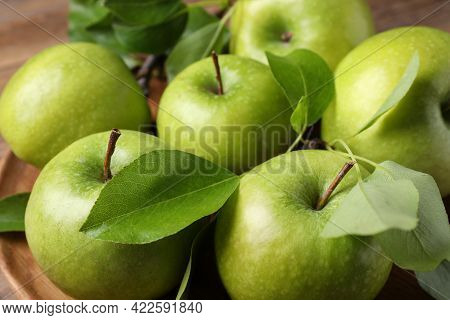Fresh Ripe Green Apples And Leaves On Wooden Plate, Closeup